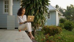 Un freelancer hermoso joven de la mujer se est? sentando en la terraza con un ordenador port?til en el fondo de su hogar almacen de video