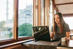 Un freelancer turístico de sexo femenino joven del blogger que trabaja en un ordenador portátil en un café en Estambul Una visión Fotos de archivo libres de regalías