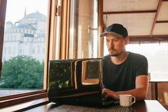 Un freelancer turístico de sexo masculino joven del blogger que trabaja en un ordenador portátil en un café en Estambul Una visió Fotos de archivo