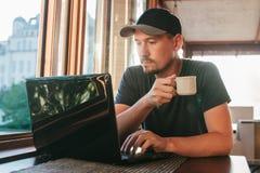 Un freelancer turístico de sexo masculino joven del blogger que trabaja en un ordenador portátil en un café en Estambul Una visió Imagenes de archivo