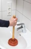 Un fregadero del cuarto de baño de Using Plunger In del fontanero imagenes de archivo