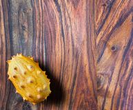 Un fruit exotique de kiwano sur en bas à gauche d'un contexte en bois images libres de droits
