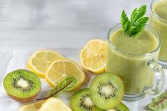 Un frullato appena preparato del kiwi, del limone, dell'arancia e del prezzemolo su una tavola del cemento Alimento del vegetaria fotografia stock libera da diritti