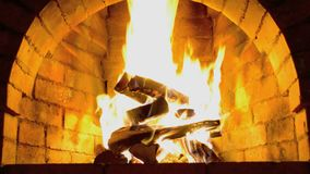 Un fuego caliente quema en una chimenea de piedra metrajes