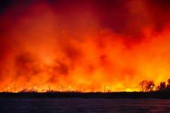 Un fuego grande en un campo cerca del agua Imágenes de archivo libres de regalías