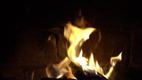 Un fuego quema en una chimenea del ladrillo, mantiene caliente metrajes