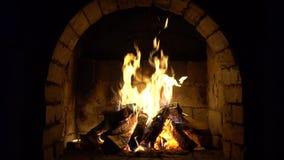 Un fuego quema en una chimenea del ladrillo, mantiene caliente almacen de metraje de vídeo