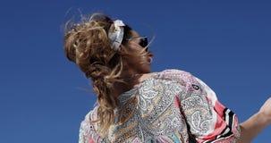 Un fuerte viento sopla en el modelo de la belleza en un vestido elegante y gafas de sol en un yate metrajes