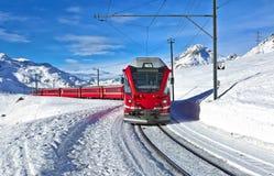 Un funcionamiento de tren suizo rojo a través de la nieve Imagen de archivo libre de regalías