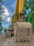 Un funcionamiento del dormilón del excavador en sitio de la construcción de carreteras fotografía de archivo libre de regalías