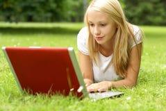 Un funcionamiento rubio joven y atractivo en una computadora portátil Fotografía de archivo libre de regalías