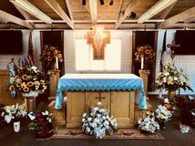 Un funerale è preparato in una chiesa con un incrocio, i fiori e una bandiera fotografie stock