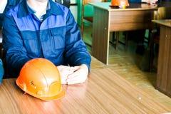 Un funzionamento dell'uomo come ingegnere con un casco di giallo arancio sulla tavola sta studiando, scrivente in un taccuino in  immagini stock