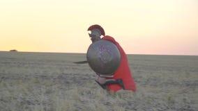 Un funzionamento di due gladiatori verso a vicenda e comincia a battersi con l'alba del backgound delle spade, movimento lento archivi video