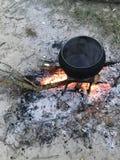 Un fuoco diluito Un vaso di cibo cotto che sta sul fuoco Immagini Stock Libere da Diritti