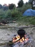 Un fuoco diluito Un vaso di cibo cotto che sta sul fuoco Immagine Stock