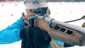 Un fusil avec son museau dans les mains d'un biathlete femelle clips vidéos