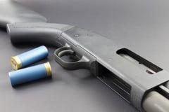 Un fusil de chasse avec les coquilles de fusil de chasse bleues Photo stock