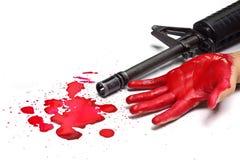Un fusil m16 avec des baisses ensanglantées de main et de sang Photos stock