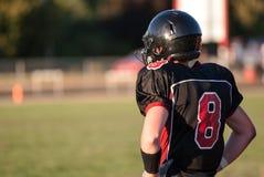 Un futbolista de la High School secundaria mira sobre el campo para el comienzo del juego Imagenes de archivo