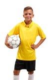 Un futbolista joven en una camiseta amarilla y pantalones cortos negros se sostiene en brazos que una bola aisló en un fondo blan Foto de archivo libre de regalías