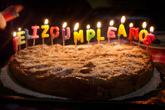 Un gâteau avec les lettres de la bougie Photos stock