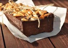 Un gâteau de chocolat appétissant décoré de petits morceaux de biscuits et placé wraped dans un papier rustique Photos stock
