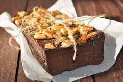 Un gâteau de chocolat appétissant décoré de petits morceaux de biscuits et placé wraped dans un papier rustique Photographie stock