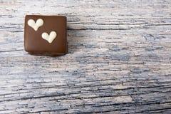 Un gâteau de chocolat avec des coeurs sur un fond en bois Photographie stock
