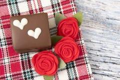 Un gâteau de chocolat avec les roses rouges Photographie stock libre de droits