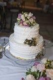 Un gâteau de mariage blanc de niveau multi sur une base argentée et des fleurs dessus Photographie stock