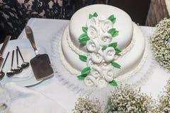 Un gâteau de mariage blanc de niveau multi sur une base argentée et des fleurs dessus Photos stock