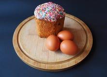Un gâteau de Pâques avec des oeufs sur le conseil photo stock