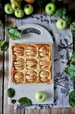 Un gâteau des pommes sur un support Autour des pommes et des feuilles fraîches de vert Photographie stock