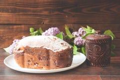 Un gâteau fait maison cuit au four épousseté avec des supports de poudre sur un conseil près d'un petit pot d'argile photos stock