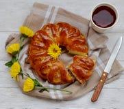Un gâteau, une tasse de café et fleurs sur la table Image libre de droits