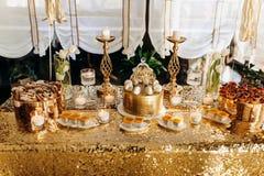 Un g?teau d'anniversaire d'or est d?cor? des macaronis photos libres de droits