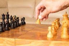 Un gage d'échecs dans une main humaine Le début du jeu d'échecs T Photos stock