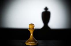 Un gage d'échecs moulant une ombre de morceau de roi dans le concept foncé de la force plus des aspirations Photographie stock libre de droits