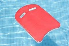 Un galleggiante rosso che galleggia nel raggruppamento blu Immagine Stock