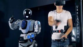 Un gamer dans des verres de VR et des bras mobiles d'un droid, fin
