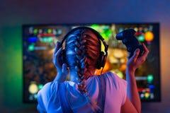 Un gamer ou une fille de flamme à la maison dans une chambre noire avec un gamepad jouant avec des amis sur les réseaux en jeux v photo libre de droits