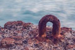 Un gancio arrugginito del metallo sul muro di cemento Fotografia Stock