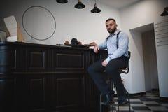 Un gangster bello in una camicia blu Un ritratto di un uccisore sicuro che si siede accanto alla pistola su un fondo bianco della immagini stock