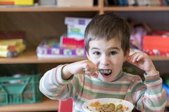 Un garçon à l'âge de 5 ans mangeant de la soupe dans le jardin d'enfants Photo libre de droits