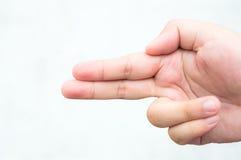 Un garçon à l'aide de sa main comme arme à feu, la tirant ou indiquant la gauche Images libres de droits