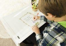 Un garçon écrivant une lettre à Santa Claus Photos libres de droits