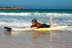 Un garçon apprend à surfer sur un conseil images libres de droits