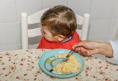 Un garçon avec un bavoir refuse de manger de la nourriture à la table de cuisine dans sa maison image stock