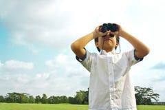 Un garçon avec des jumelles Images libres de droits